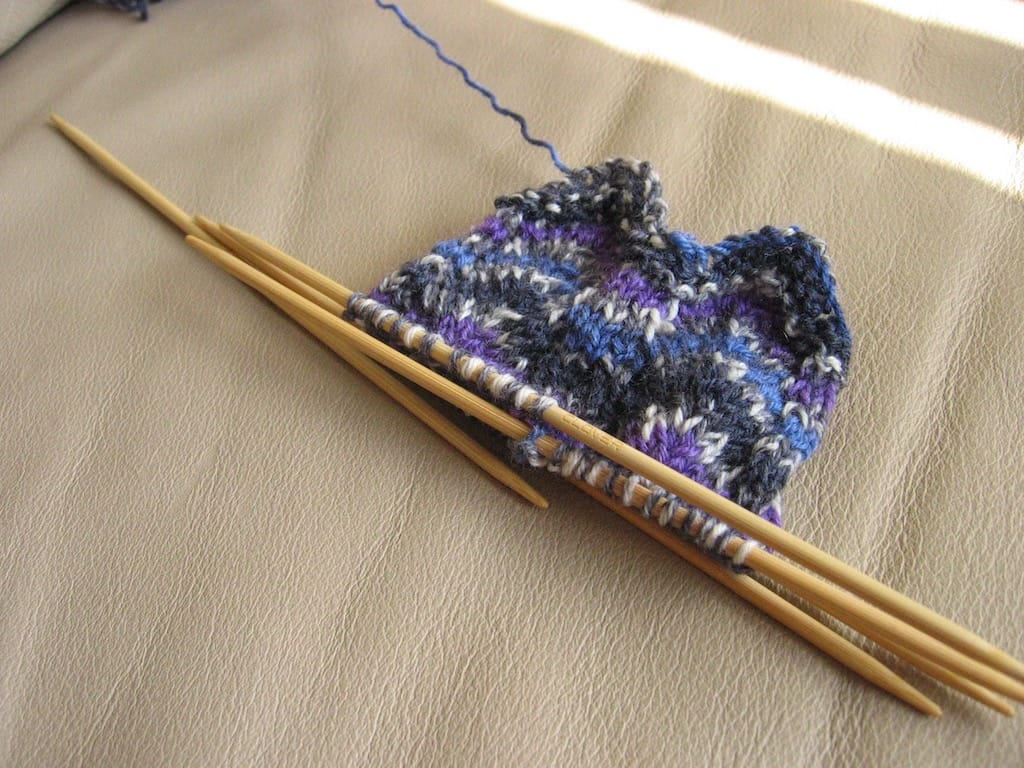 A purple hand-knit sock in progress.