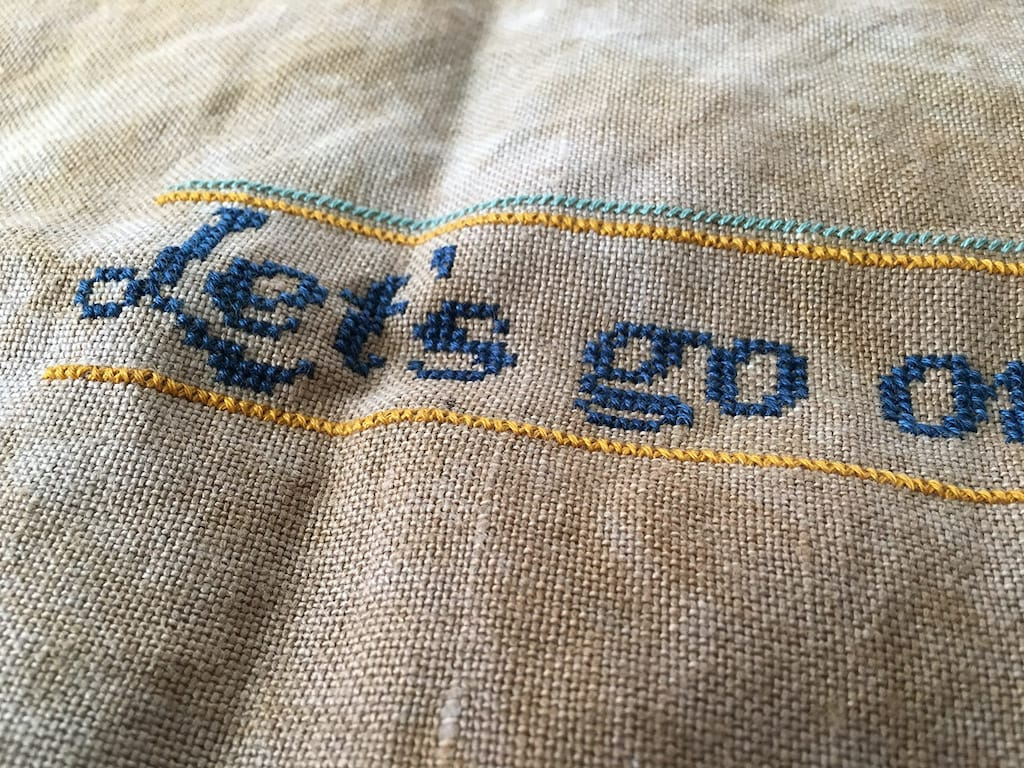 Close up of lettering on the cross-stitch piece.
