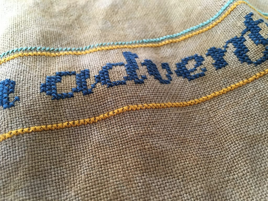 Color variations in the cross-stitch lettering.