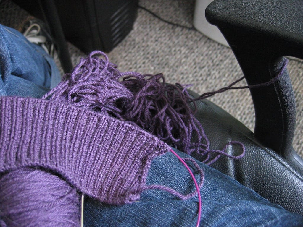 A knit cardigan tangled up in a computer chair.