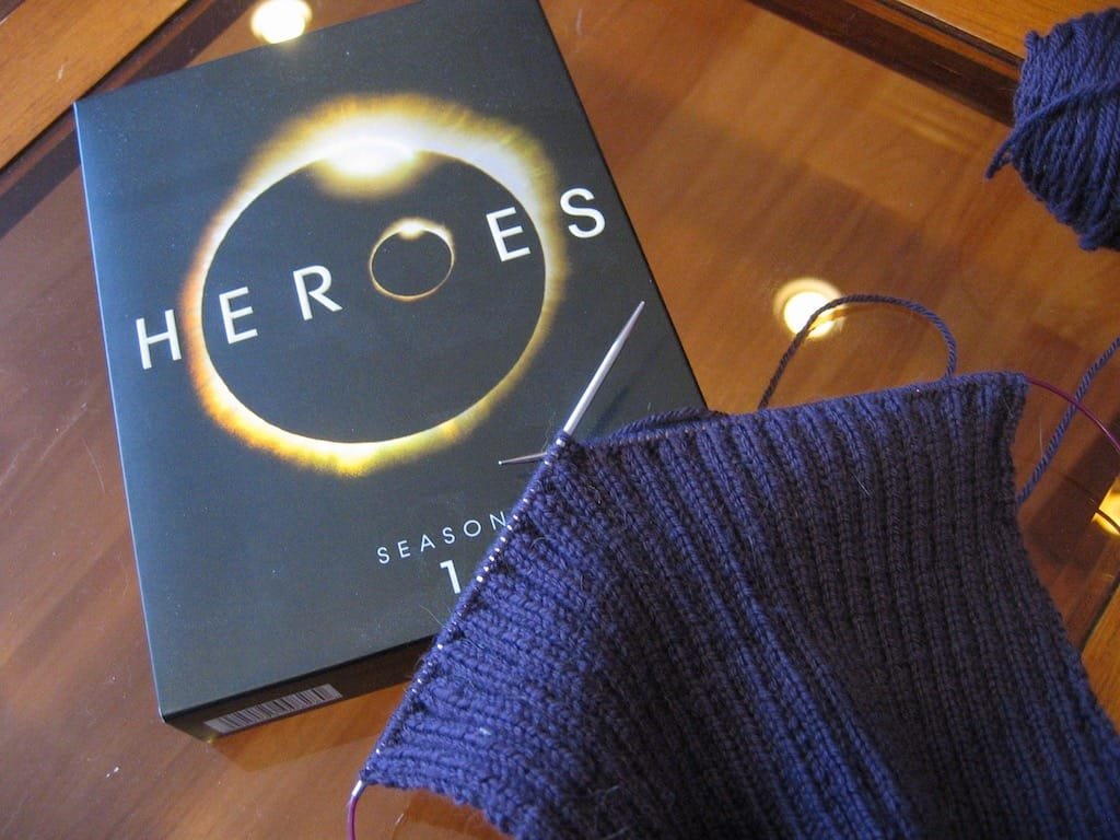 A knit cardigan in progress with the Heroes DVD.