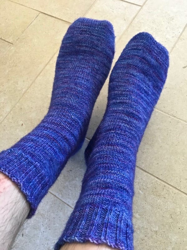 Hand knit socks on a pair of feet.