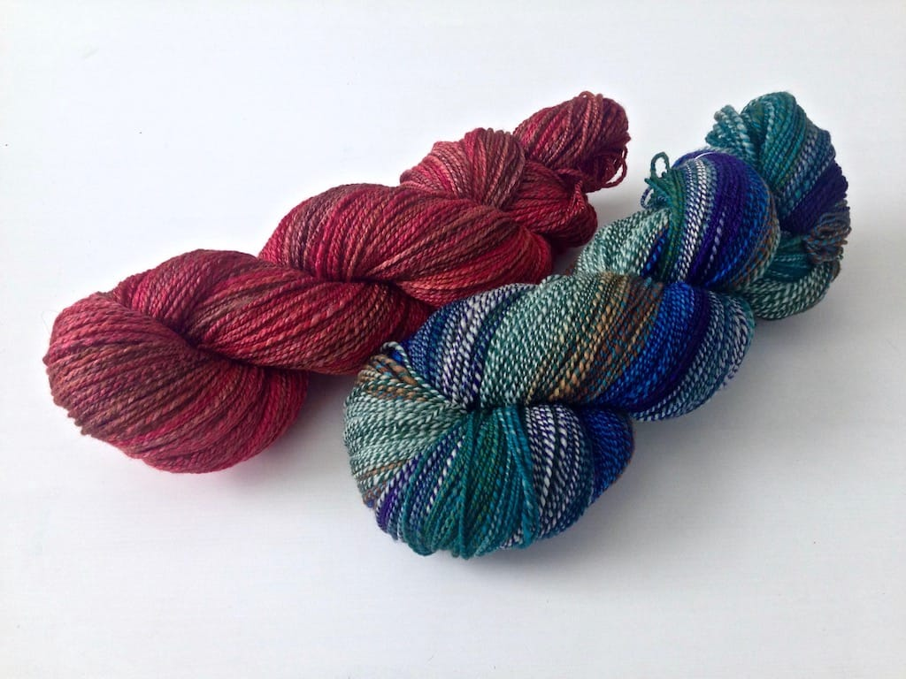 A red skein and a blue/green skein of handspun yarn.
