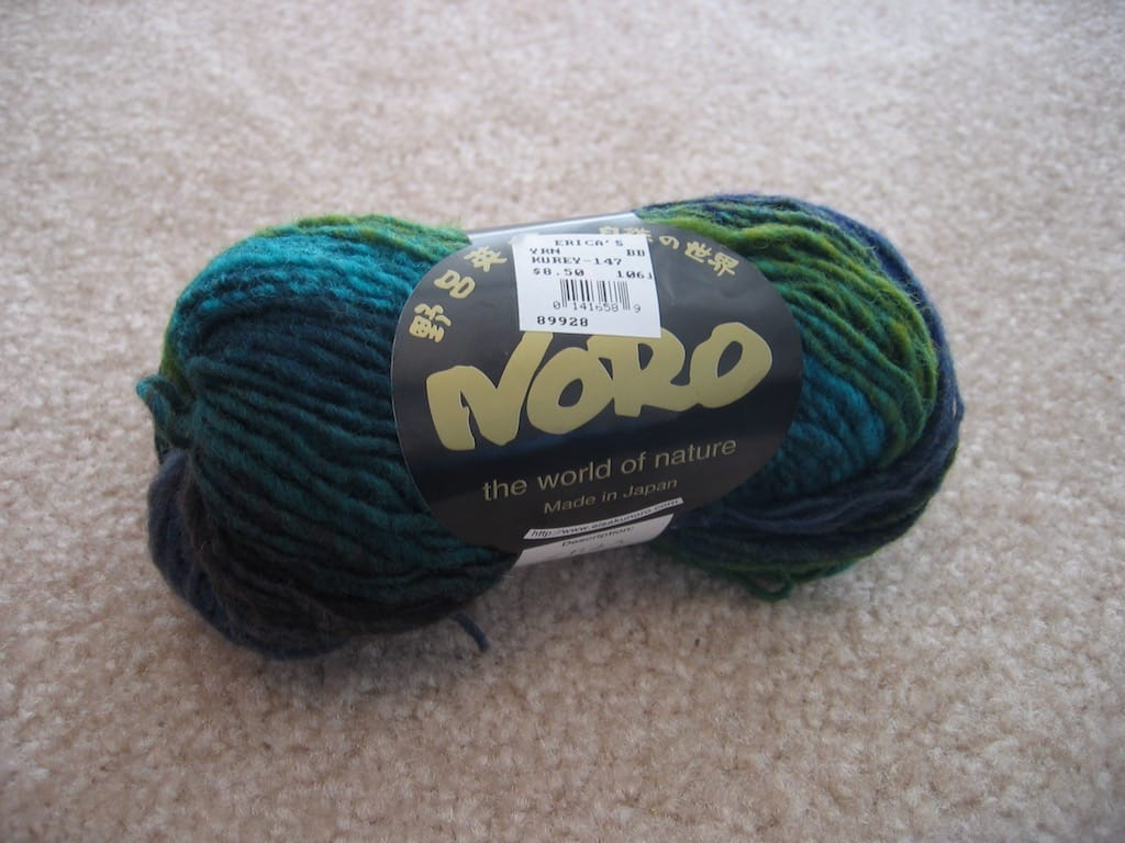 A skein of blue-green, single-ply yarn.