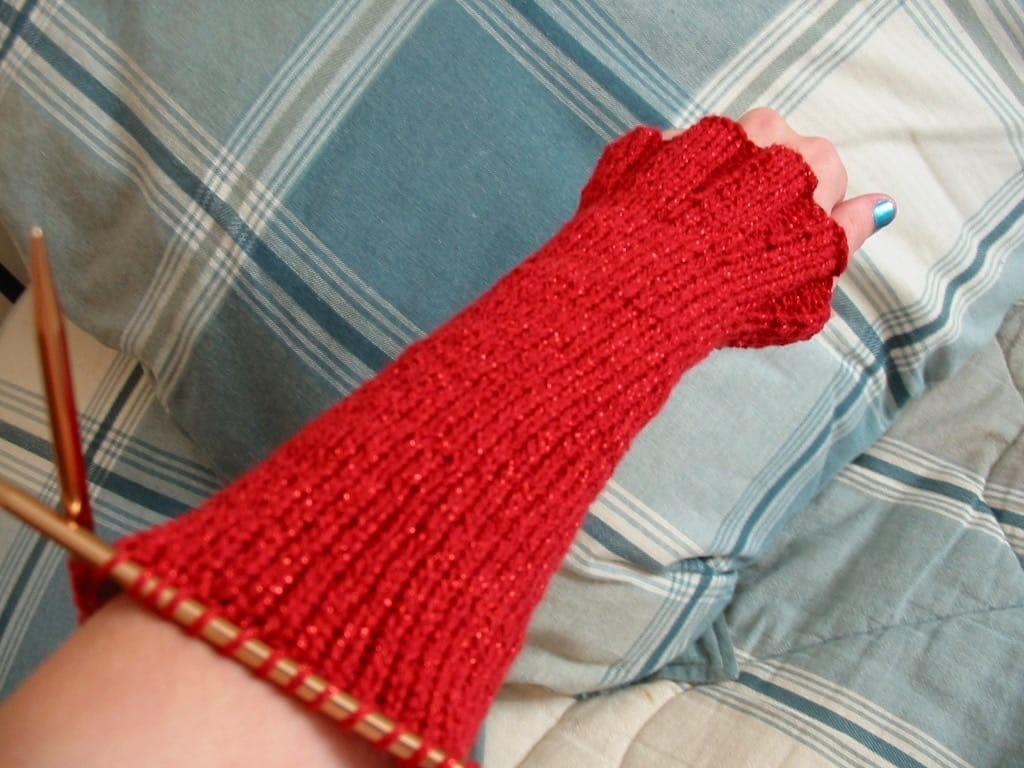 The arm of a glittery red handknit sweater.