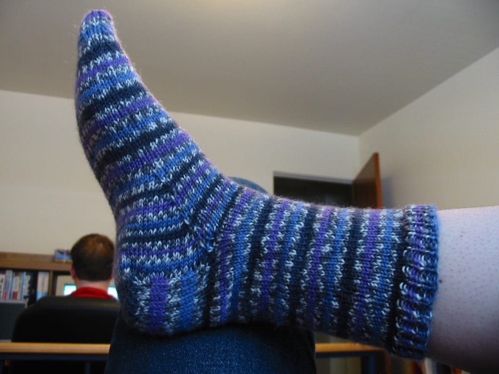 A finished purple striped sock on my foot.