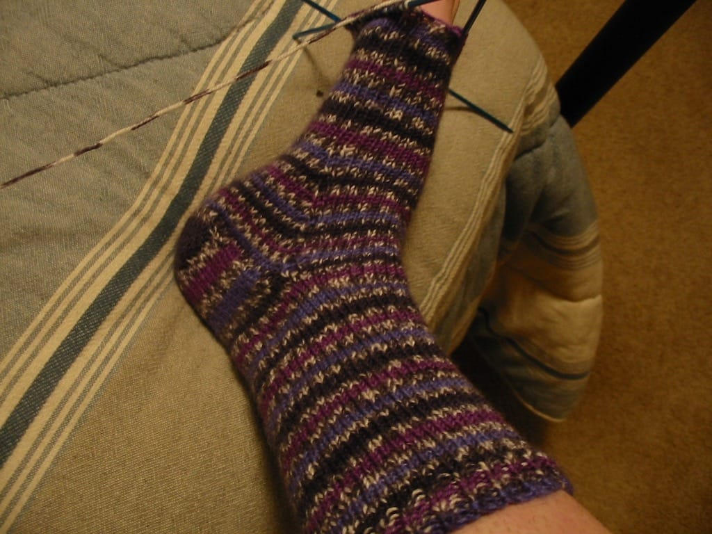 A purple striped sock minus the toes.